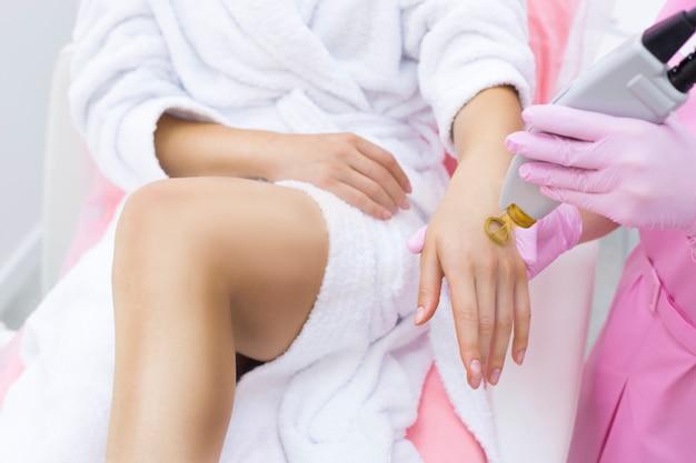 Esthéticienne fait l'épilation au laser sur la belle et mince main d'une femme dans un salon de la clinique. Photo Premium