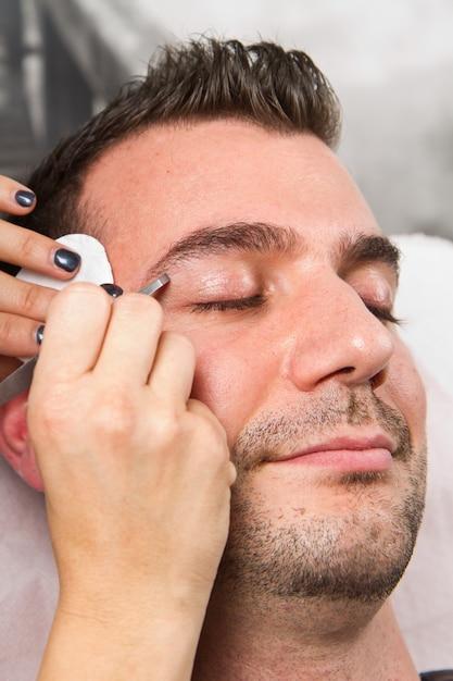 Esthéticienne En Train De Cueillir Un Homme Beau Les Sourcils Avec Une Pincette Dans Un Salon De Beauté Photo Premium