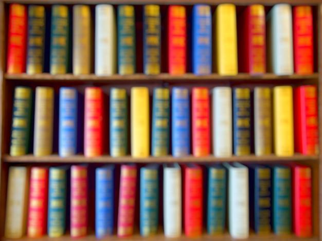 Estompée de livres colorés, manuel, littérature sur bois étagère en bibliothèque. Photo Premium