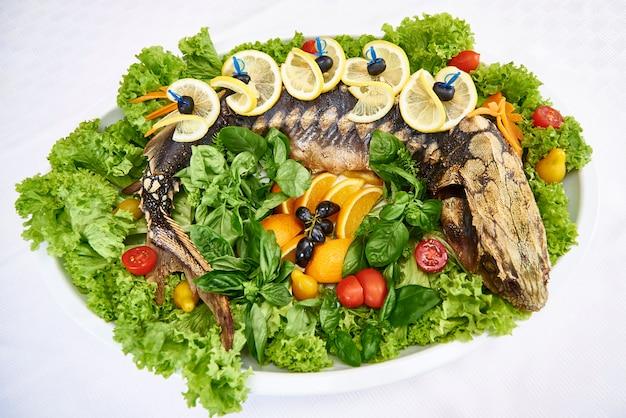 Esturgeon entier cuit au four avec feuilles de laitue fraîche, légumes et fruits. Photo Premium