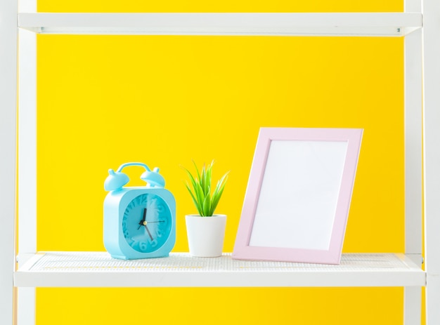 Étagère blanche avec des objets de papeterie contre jaune vif Photo Premium