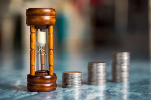 Étape des piles de pièces avec sablier ou sablier, épargne et investissement ou concept de planification familiale Photo Premium