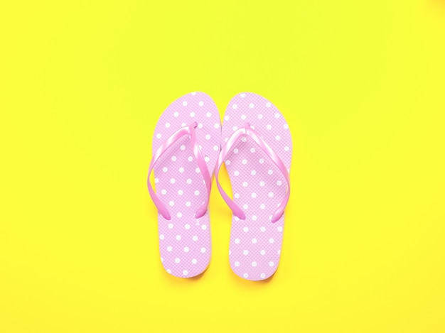 Été plat poser. accessoires de plage, tongs roses et lunettes de soleil sur fond jaune. Photo Premium