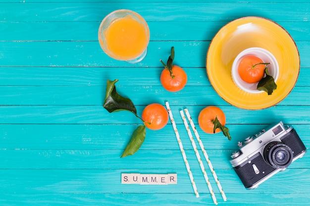 Été Sertie De Mandarines Et De Jus Et Caméra Sur Une Surface En Bois Photo gratuit