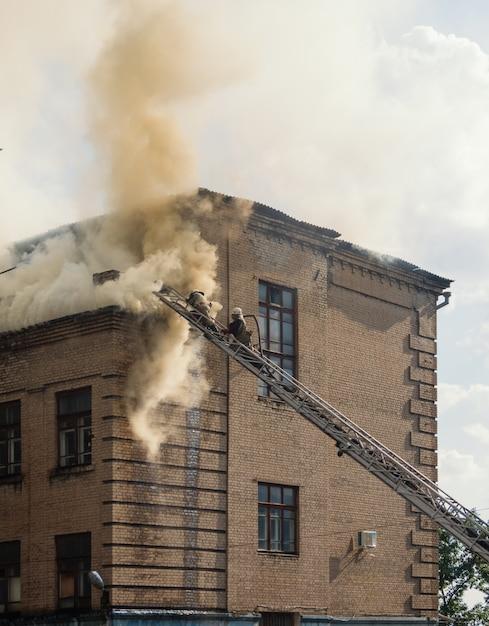 Éteindre un feu dans un vieil immeuble de trois étages Photo Premium