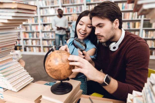 Ethnic asiatique fille et homme blanc utilisent globe. Photo Premium