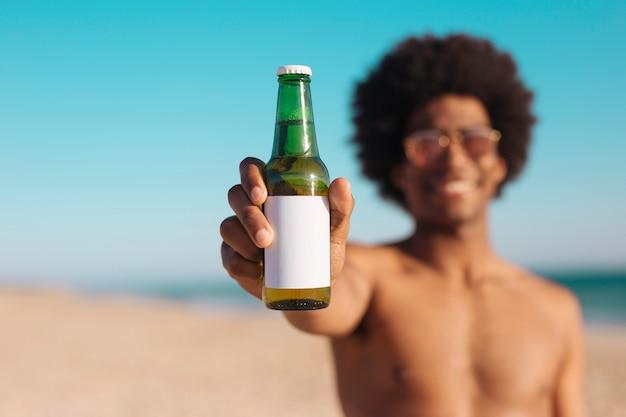 Ethnique, homme, tenue, bouteille bière Photo gratuit