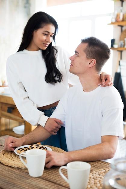 Ethnique jeune femme embrassant son petit ami assis à table Photo gratuit
