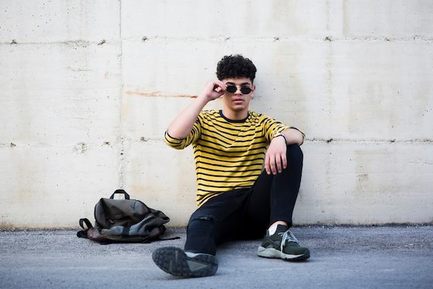 Ethnique jeune homme avec une coiffure cool assis sur l'asphalte Photo gratuit