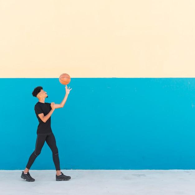 Ethnique mâle spinning basketball sur le doigt Photo gratuit