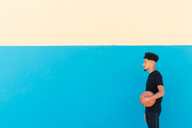 Ethnique sportif avec cheveux bouclés debout avec basket Photo gratuit
