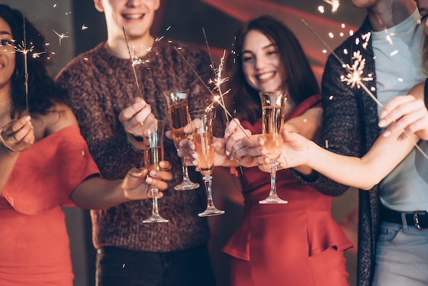 Des étincelles partout. des amis multiraciaux célèbrent le nouvel an en tenant des feux de bengale et des verres à boire Photo Premium