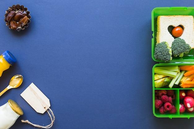Étiquette et nourriture près de la boîte à lunch Photo gratuit