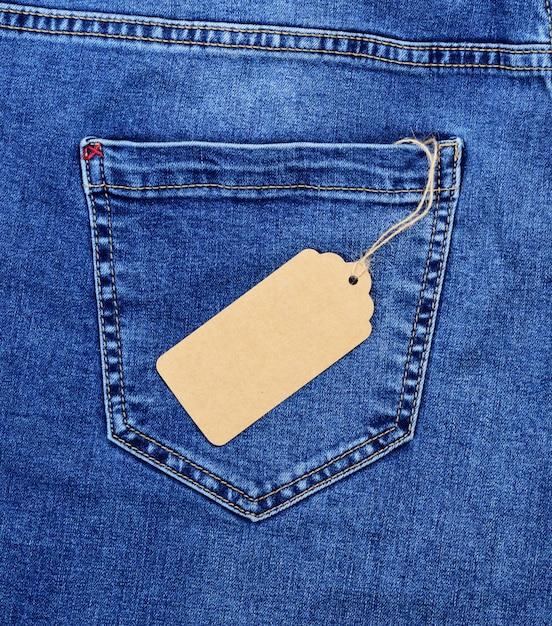 Étiquette de prix vierge en papier brun sur une corde contre la poche arrière du blue jeans Photo Premium