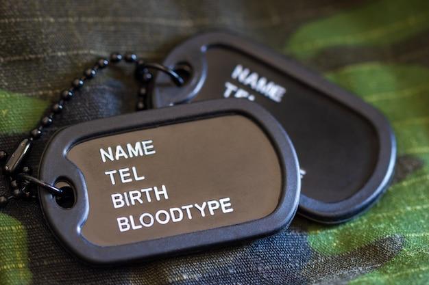 Étiquette de soldat ou de chien posée sur une veste militaire et au soleil du matin. Photo Premium