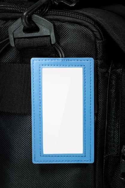 Étiquette suspendue en cuir bleu sur fond de sac de voyage. étiquette de nom vide pour votre conception. Photo Premium