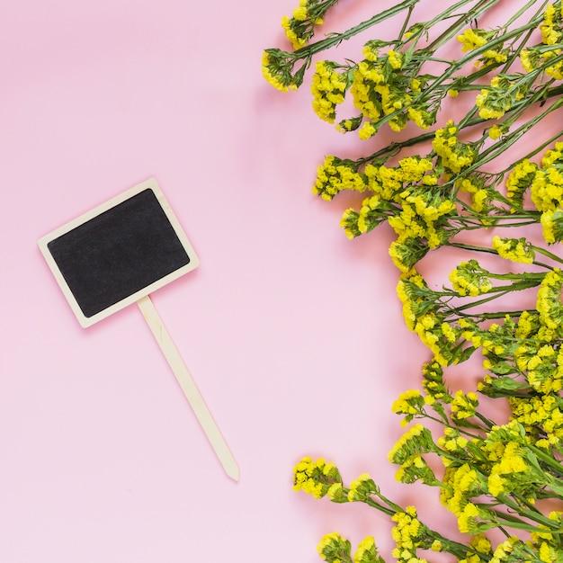 Une étiquette de tableau blanc et des fleurs jaunes sur fond rose Photo gratuit