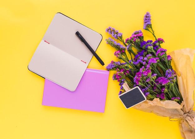 Étiquette de tableau noir; fleurs pourpres; agenda et stylo sur fond jaune Photo gratuit