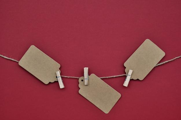 Les étiquettes en papier sont attachées avec des épingles à linge à la corde en rouge. Photo Premium
