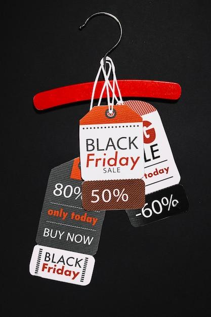 Étiquettes de vendredi noir sur un cintre en bois rouge Photo gratuit