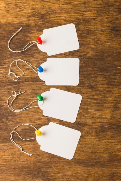 Étiquettes vierges attachées avec des punaises colorées sur une surface en bois texturée Photo gratuit