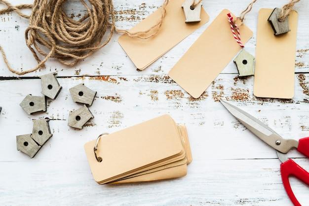 Étiquettes vierges; ciseaux; ficelle et petites nichoirs sur un bureau blanc Photo gratuit