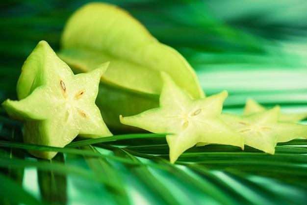 Étoile exotique ou averrhoa carambola sur feuilles de palmier vert tropical sur fond turquoise. Photo Premium