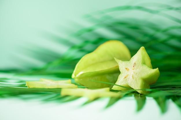 Étoile exotique ou averrhoa carambola sur feuilles de palmier vert tropical Photo Premium