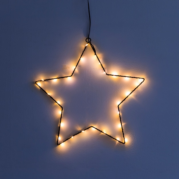 Étoile en guirlande sur mur Photo gratuit