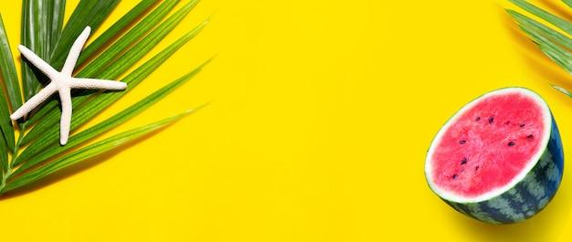 Étoile De Mer Sur Les Feuilles De Palmiers Tropicaux Avec Pastèque Sur Fond Jaune. Profitez Du Concept De Vacances D'été. Vue De Dessus Photo Premium
