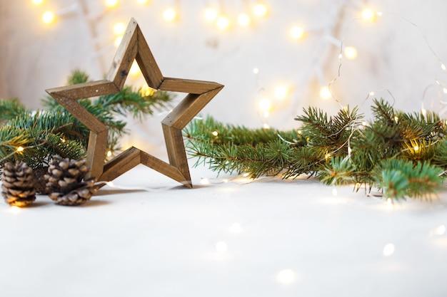 Étoile de noël, branches de sapin, décorations du nouvel an, bloc-notes à la lumière Photo Premium