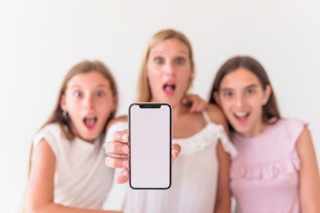 Étonnée mère et filles tenant un smartphone avec écran blanc Photo gratuit