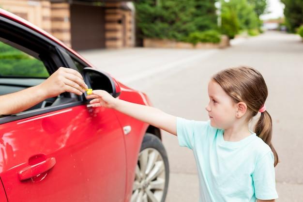 Étranger dans la voiture offre des bonbons à l'enfant. les enfants en danger. concept d'enlèvement d'enfants. Photo Premium