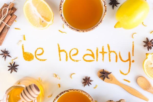 Être en bonne santé - écrit à partir de curcuma moulu sur un fond blanc Photo Premium