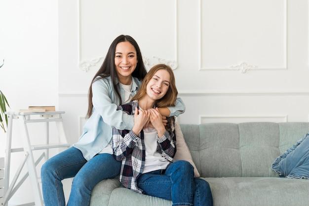 Étreindre mes dames assis sur un canapé et souriant Photo gratuit