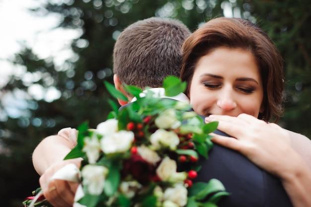 Étreinte romantique des jeunes mariés. couple se promène dans le parc. Photo Premium