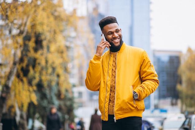 Étudiant afro-américain marchant dans la rue et parler au téléphone Photo gratuit