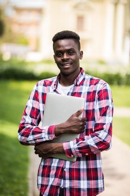 Étudiant Afro-américain Avec Ordinateur Portable Dans La Journée Ensoleillée Sur La Rue De La Ville Photo gratuit