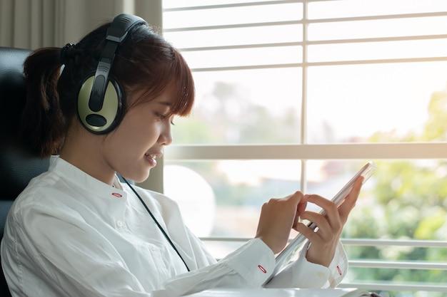 Étudiant en apprentissage concept d'étude en ligne: belle fille asiatique à l'écoute avec un casque Photo Premium