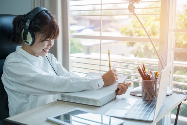 Étudiant en apprentissage concept d'étude en ligne: belle fille asiatique écoute avec des écouteurs et un ordinateur portable Photo Premium