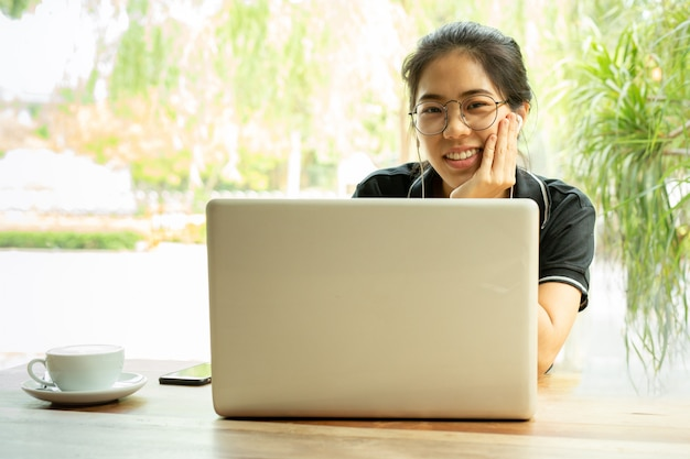 Étudiant asiatique femme travaillant sur ordinateur portable avec écouteur en regardant la caméra. Photo Premium