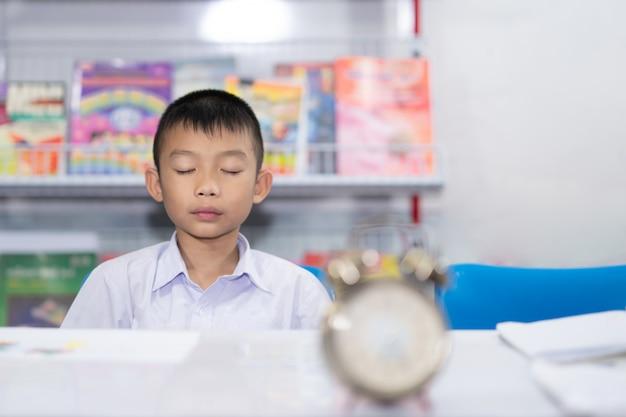 Étudiant asiatique mignon étudiant méditant sur horloge floue et livre sur fond blanc Photo Premium