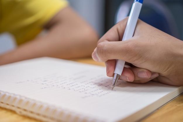 Étudiant asiatique note sur le cahier tout en apprenant à étudier et à écrire pour planifier le travail Photo Premium