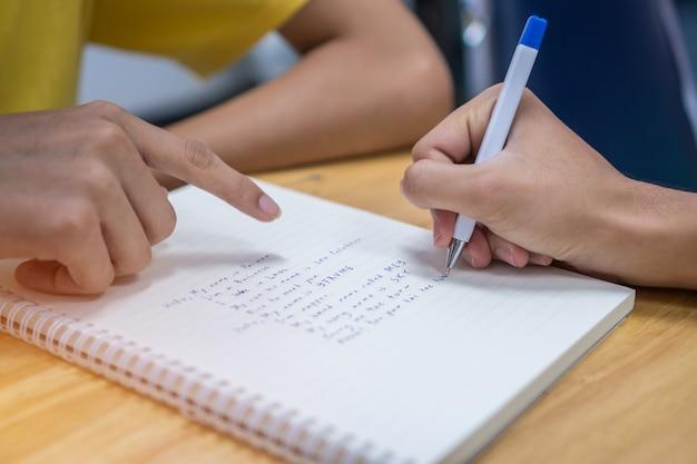 Étudiant asiatique note sur le cahier tout en apprenant à étudier et à rédiger pour planifier Photo Premium