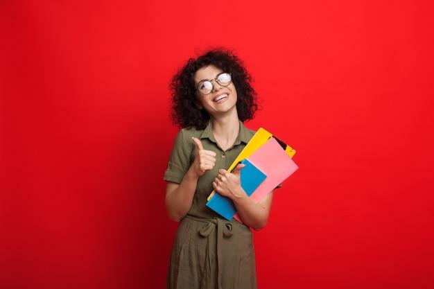 Étudiant Caucasien Aux Cheveux Bouclés Tient Des Livres Et Fait Des Gestes Le Signe Similaire Tout En Posant Sur Un Mur Rouge Photo Premium