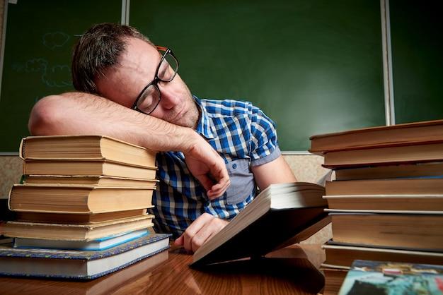 Un étudiant décoiffé, fatigué et torturé, à lunettes, dort à la table sur une pile de livres au fond du tableau. Photo Premium