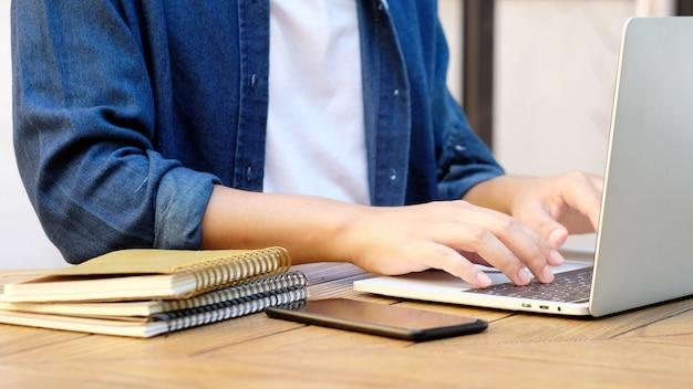 Étudiant écrit Sur Ordinateur Portable Tout En Utilisant Un Ordinateur Portable Photo Premium