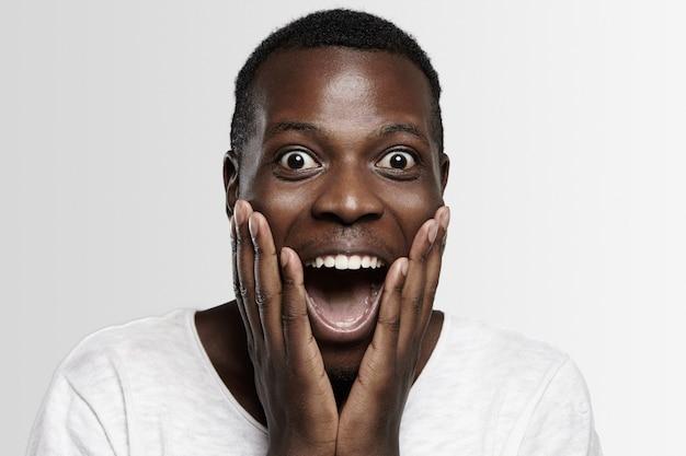 Étudiant Ou Employé Africain Choqué En Pleine Incrédulité, Les Mains Sur Les Joues, La Bouche Grande Ouverte, Surpris Par Des Nouvelles Inattendues Ou Des Prix De Vente élevés. Photo gratuit
