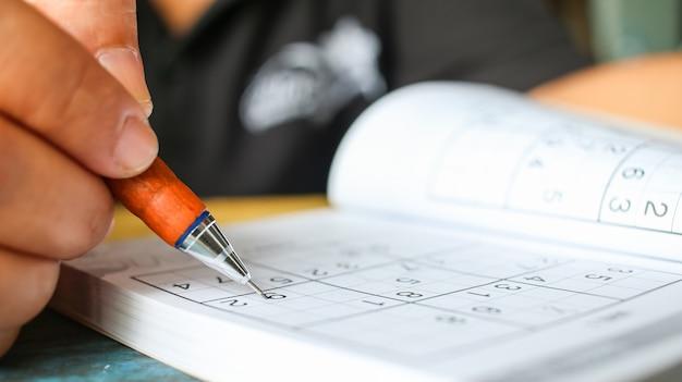 L'étudiant essaie de résoudre le sudoku avec un crayon de couleur comme passe-temps à l'extérieur Photo Premium