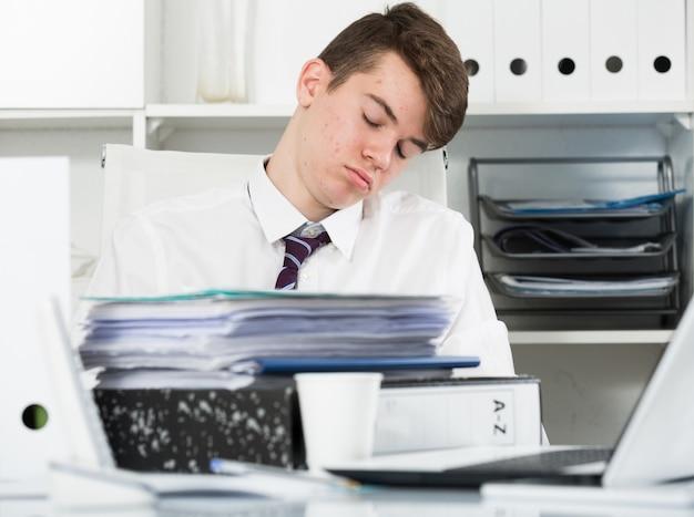 Étudiant fatigué de travailler et dormir dans le bureau